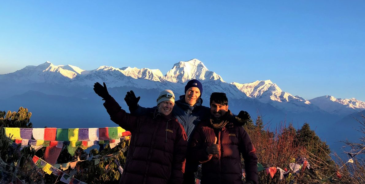 Heaven Himalaya guide with guests posing for a photograph at Poonhill