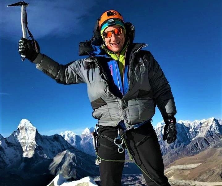 A man standing at the top of Island Peak after the successful summit of Island Peak