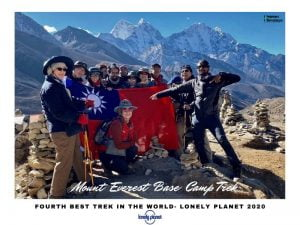 A group of trekkers with a country flag in everest base camp